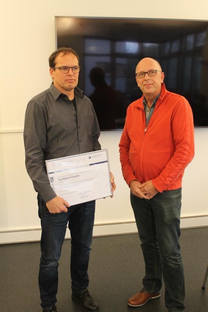 Tischlermeister Arno Frerichs erhielt zum 50-jährigen Geschäftsjubiläum eine Urkunde überreicht.